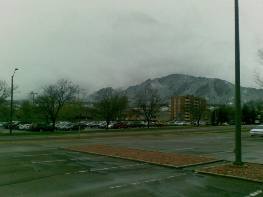 I like this photo because it shows that Boulder is still a regular old town - parking lots, streetlights, ugly apartment buildings, and rain.  But look at the mountains!