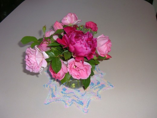 Cabbage Roses create a pink back drop for one darker pink Peony. The folage comes from the Rose bushes.  I clip off the thorns and strip the bottom leaves before placing the flowers in the vase.