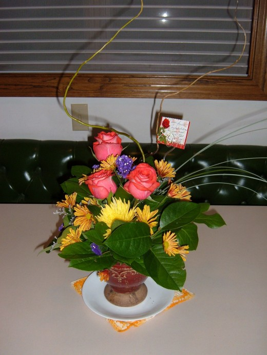 "This bouquet was given to me after the publication of our children's book: ""The Three Betty Goats Griff"".  It is a mixed arrangement in an antique vessel. Notice the large waxy leaves that are used as a backdrop to the Roses & Daisies."