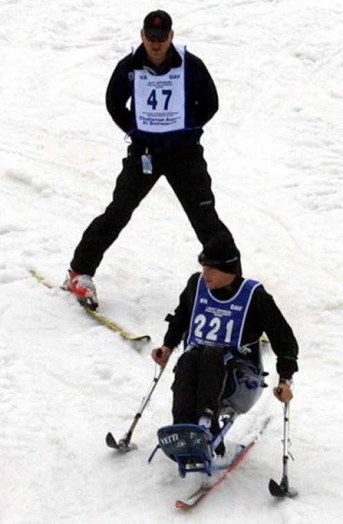 Cpl. Brian Wilhelm uses a mono-ski at the annual National Disabled Veterans Winter Sports Clinic, April 4-9 at Snowmass Village CO. Capt. David Rozelle, behind him, lost his right foot after a land mine explosion.