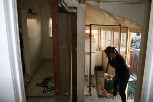 Taking down the wall between the old, tiny bath and the covered porch.  We leveled the floor, installed reclaimed flooring,