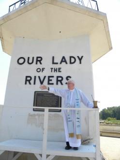 The Rev. Banken bestows  blessings on passing boats