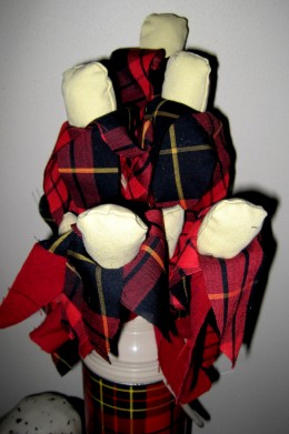 Re-purposed plaid thermos used as vase for fabric flowers.