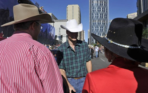 Prince William (C) greets Canada's Prime Minister Stephen Harper (L) and his wife Laureen at the official start of the Calgary Stampede parade in Calgary, Alberta