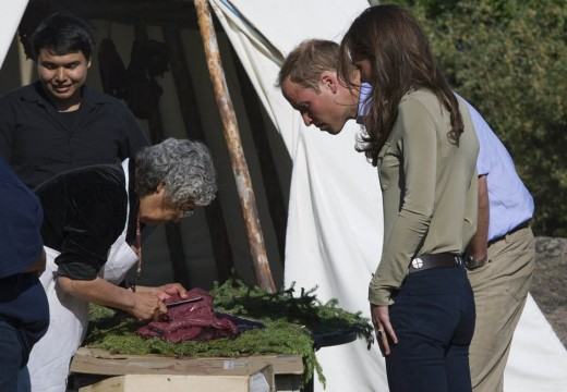 William and Catherine watch a woman prepare caribou meat for smoking while visiting Blatchford Lake, Northwest Territories