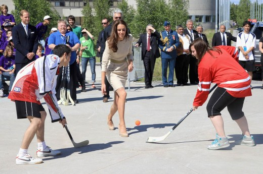 Catherine throws a hockey puck during an official welcome ceremony at the Somba K'e Civic Plaza in Yellowknife