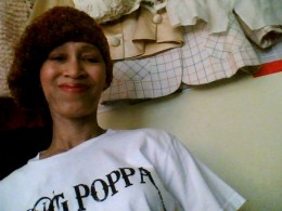 "Victoria Moore in a ""Yung Poppa"" t-shirt and a brown tam made by Naomi Y. of Los Angeles, CA. for ""The Giving Caps Group""."