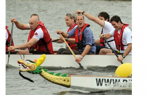 Prince William celebrates winning a dragon boat race as he competed against his wife across the Dalvay lake in Charlottetown