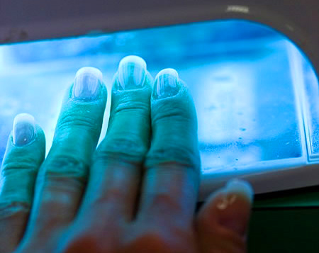 Gel nails being cured under a UV light