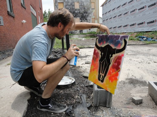 Image of Kyle Maier spray painting a longhorn skull on canvas created with stencils.  Note the vacant lot where the Civil War chapel once stood, and the fire-damaged apartment building to the rear.