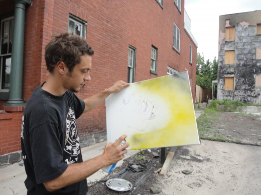 Image of Eric Stahl working on one of his free-hand paintings of the sun adjacent to The Ragged Edge coffee house.