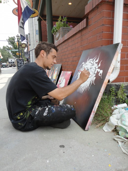 Image of Eric Stahl working on a painting of the sun on the sidewalk in front of The Ragged Edge coffee house.