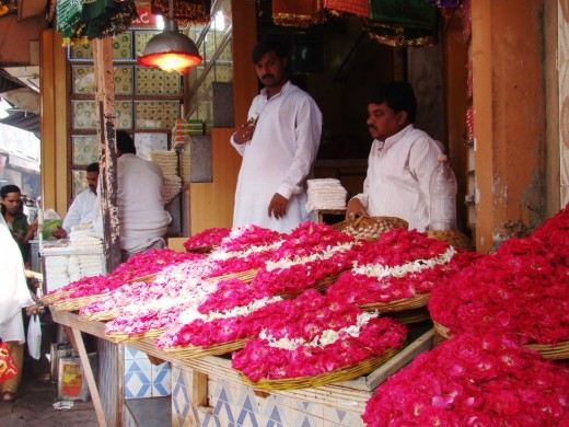 Shopkeepers waiting for prospective buyers with offerings of flowers, mainly red & pink  roses