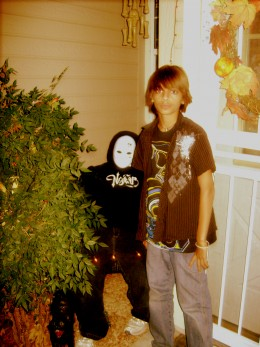 This is my son Jerryd standing next to Fred our Halloween dummy who sits in a chair next to our door every year. He is made from news paper, clothes and a white drama mask. No one can ever tell if he is a person or fake.