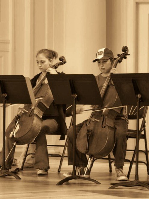 Cello players hold the cello between their knees and rest the spike on the floor. The spike supporting the cello can be adjusted to the height needed by the cellist.