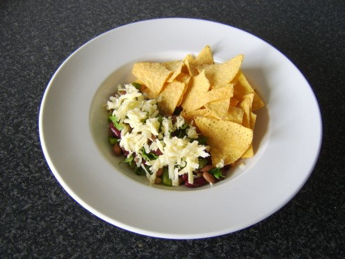 Mexican three bean salad served with cheese and tortilla chips