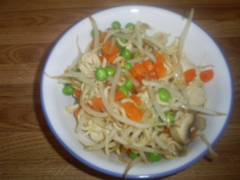 The finished chicken stirfry that contains ichiban noodles, bean sprouts, carrots, and peas.