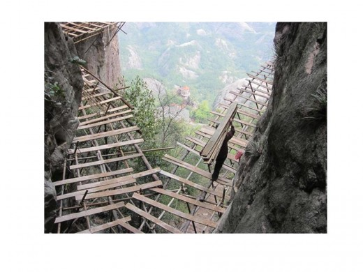 Workers build a footpath around the vertiginous slopes of Shifou Mountain in China