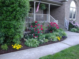 Concrete pavers provide another level of plants close to the porch where a birdbath is cleverly placed.