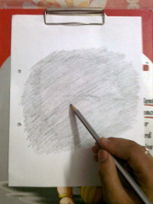 Holding the pencil and scratching on the paper.