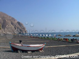 The famous beach of Perissa and the enormous rock of Mesa Vouno on Santorini Greece.
