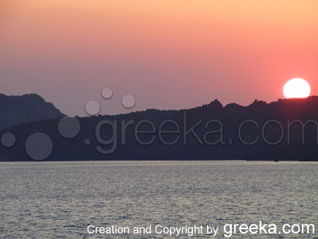 Pictures of Santorini : A sunset behind the famous submeged volcano of the island of Santorini Greece.