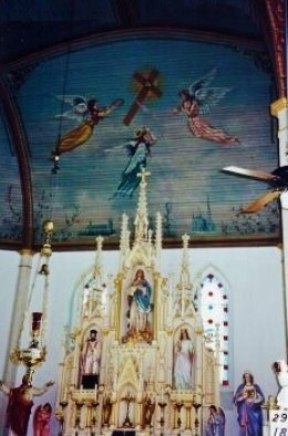 "At the base of the mural above  the altar are paintings of 2 religious buildings in the ""old country."""