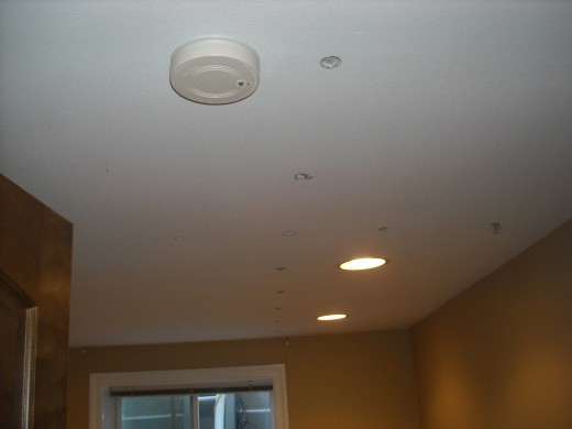 Holes are drilled into the ceiling to gain access so that the ceiling cavities can be dense packed with cellulose insulation.