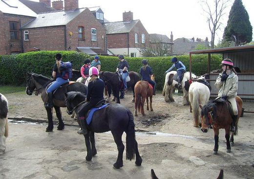 Riders wait in the yard before they go out for a hack at the Gertrude Road stables in Lady Bay, Nottingham