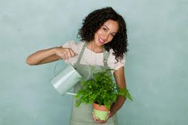 It may be better to have your house plant on a flat surface when watering.  However, it's ok to water while holding your house plant, if you like. Just  wear gloves or make sure you have the bottom covered so your hands will not get wet or soiled!