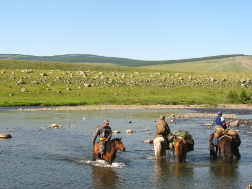 Mongolian horsemen paddle through water during the trip which was the inspiration for the Horse Boy movie