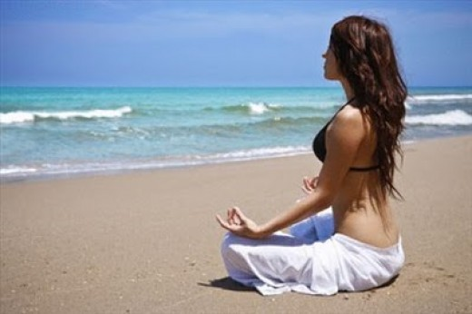 A woman meditates by the sea. Meditation can be used as effective pain relief for Rheumatoid Arthritis