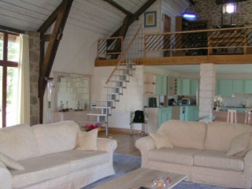 The same barn as above showing the interior converted.  A spectacular vaulted room with mezzanine, retaining all the original beams and some stone walls. Window to front. contemporary open style staircase to mezzanine & cloakroom. Solid pine floor an