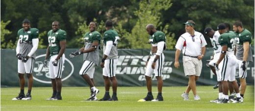 New York Jets general manager Mike Tannenbaum, in tan shorts at center right, walks near Jets players who recently signed contracts with the team, during NFL football training camp Thursday, Aug. 4, 2011, in Florham Park, N.J. The players were able t
