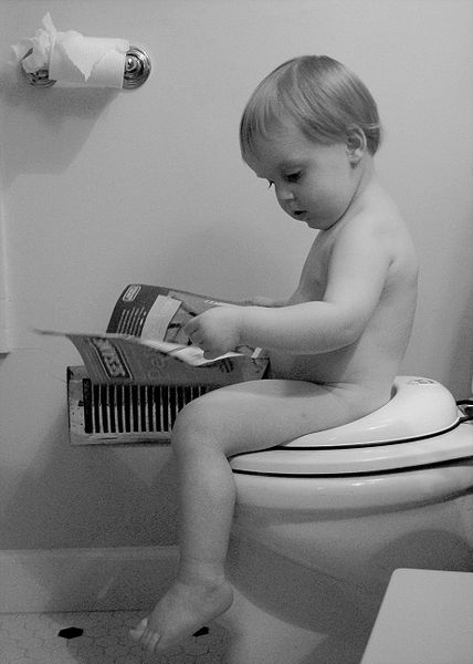 Baby reading while sitting on a toilet