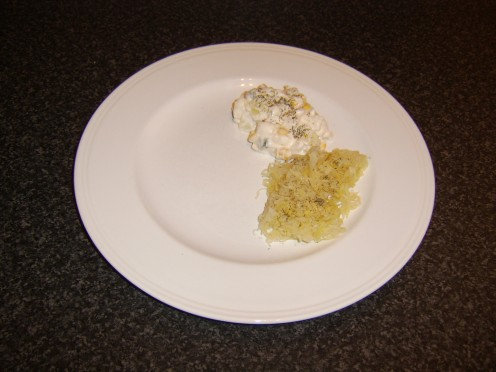 Potato salad and sauerkraut are added to the serving plate and garnished with an optional scattering of freshly chopped dill