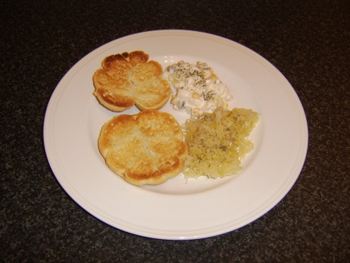 Toasted bread roll halves are added to the plate, cut side uppermost