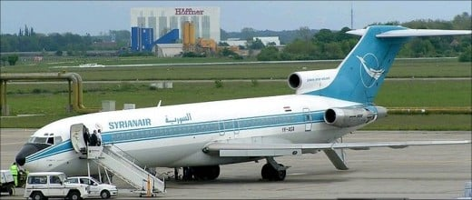 A boeing 727 with it's aft doorstair deployed and clearly visible at the rear of the aircraft