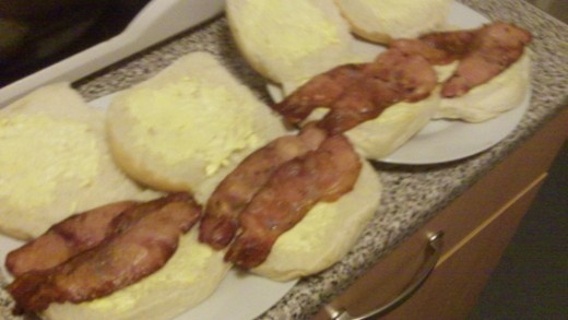 Lay the bacon gently onto the bread baps, if you don't like bacon poking out of the bap fold it and tuck it into bed!
