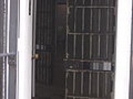 "A view of the door to a maximum security cell in the Old Montana Prison, displaying the screen on the outside of the bars to protect guards from the sloshing of the ""honey bucket"""