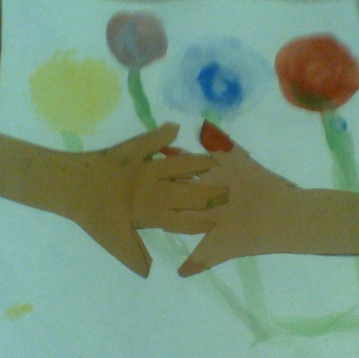 multimedia picture of friends holding hands around a bouquet of flowers