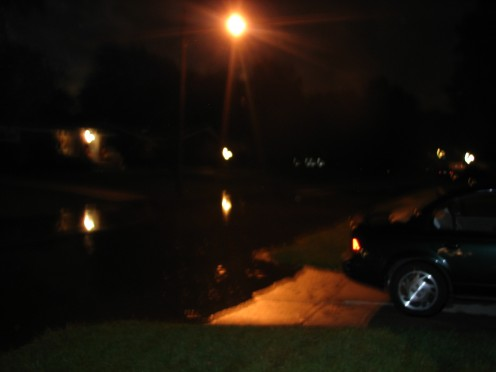 Night time falls on flooded streets and the river is still rising.