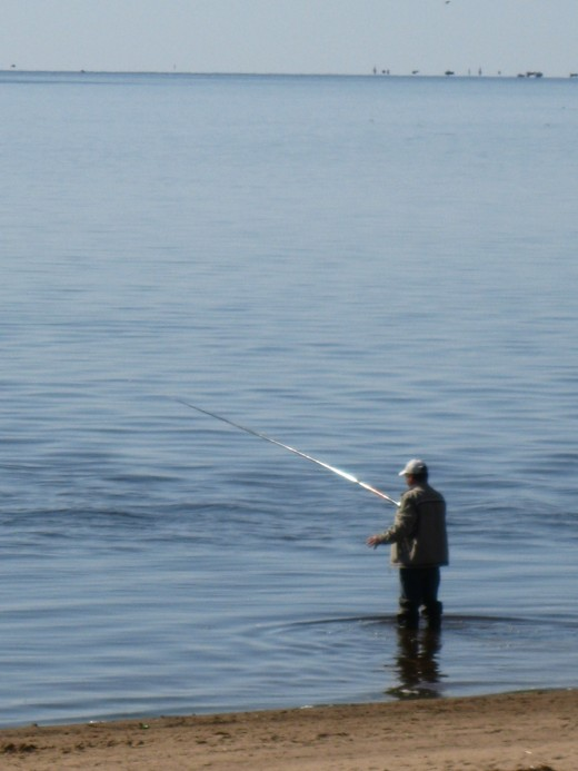 Man fishing in Lake Ilmen outside walls of St George Monastery near Veliky Novgorod, Russia