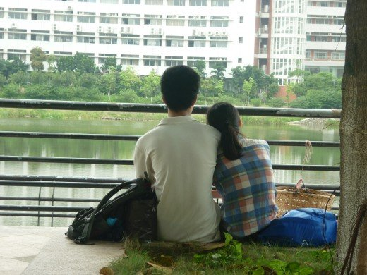 A couple cuddling by a lagoon under the shade during a hot day