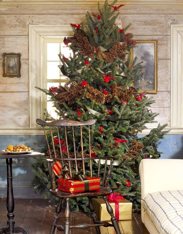 Rustic Christmas tree with pine cone garlands and red cardinal birds.