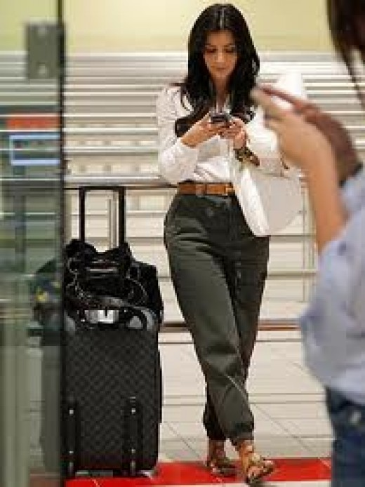 Kim Kardashian is checking her messages.  She should be closer to her luggage and be more attentive to her surroundings!
