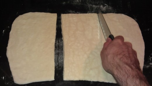 Cut the rolled-out dough into thirds.