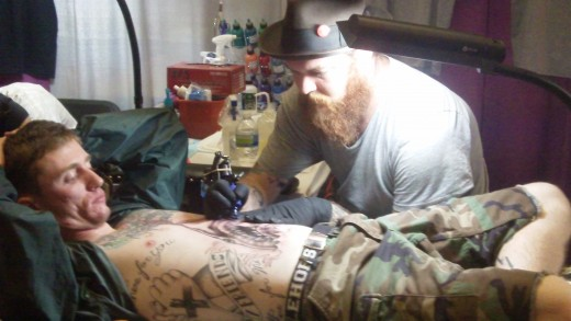 Johnny Awesome of Smoking Guns Tattoo works on a client.