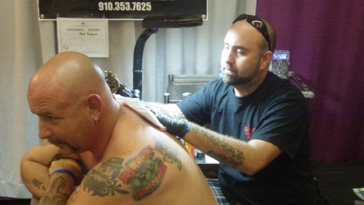 Bart Andrews of Bombs Away Tattoo, working on Robert Forsch. Bart earned three awards for new tattoos applied at the convention.