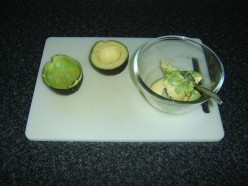 The flesh is carefully scooped out of the avocado halves with a teaspoon